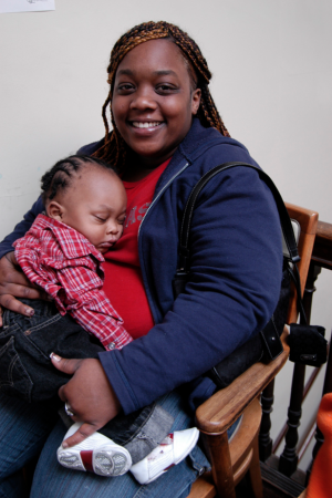 A person is sitting with a child in their lap and smiling