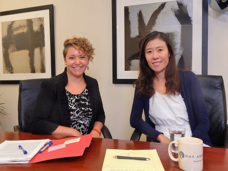 """Yan (right), seated with her attorney, shares her advice to other survivors: """"Be brave; speak up; and seek help from organizations like BayLegal."""""""