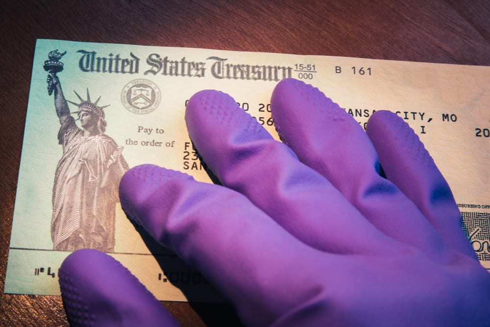 A purple-gloved hand lays on top of a check from the U.S. Treasury