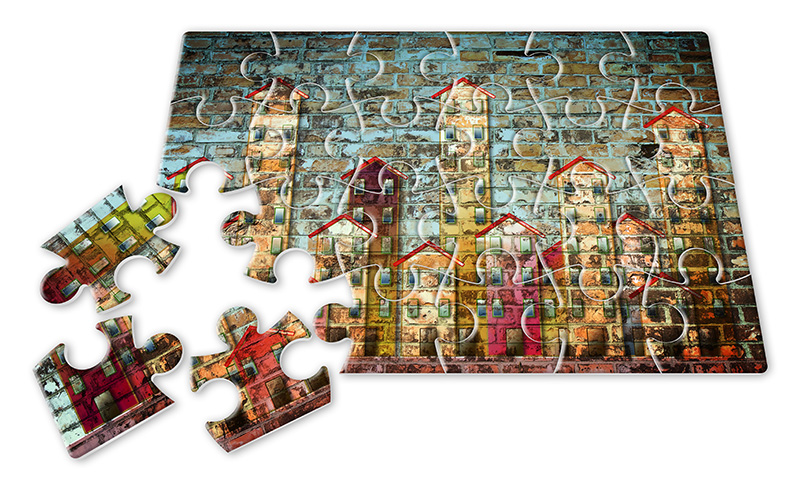 A jigsaw puzzle of a housing complex with three loose pieces in the left bottom corner