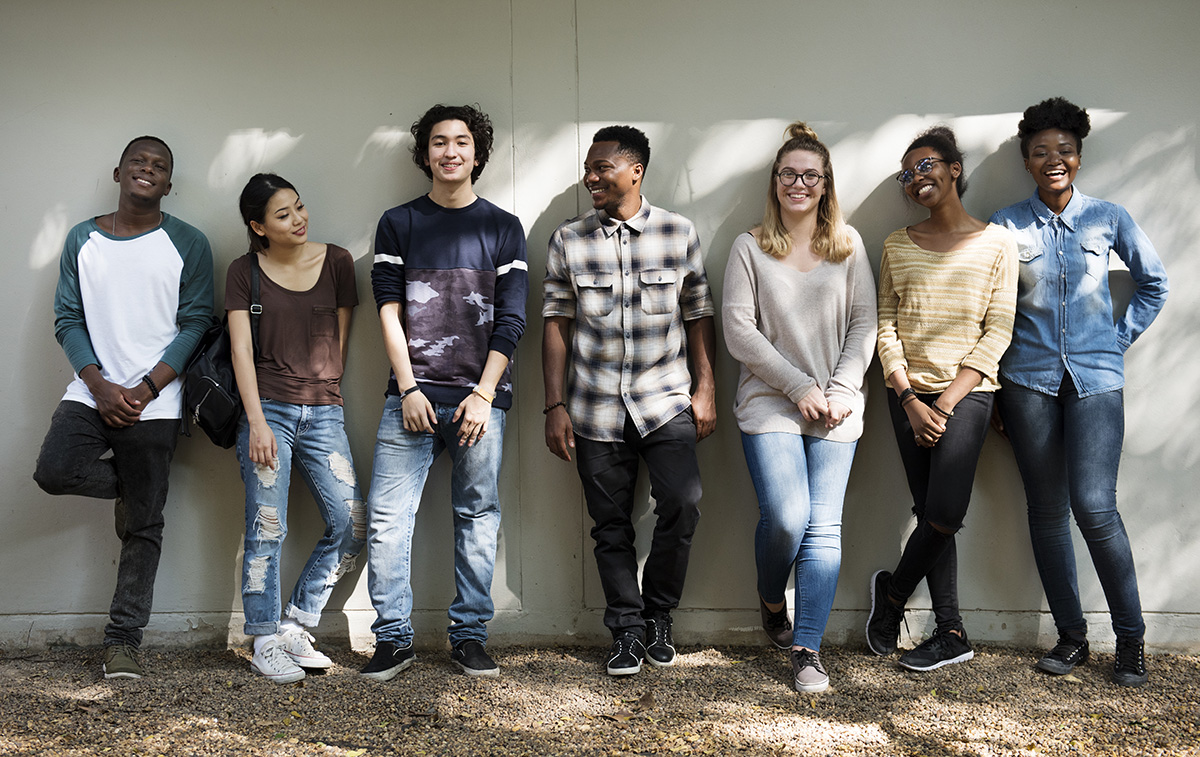 Seven young people lounge against a wall smiling