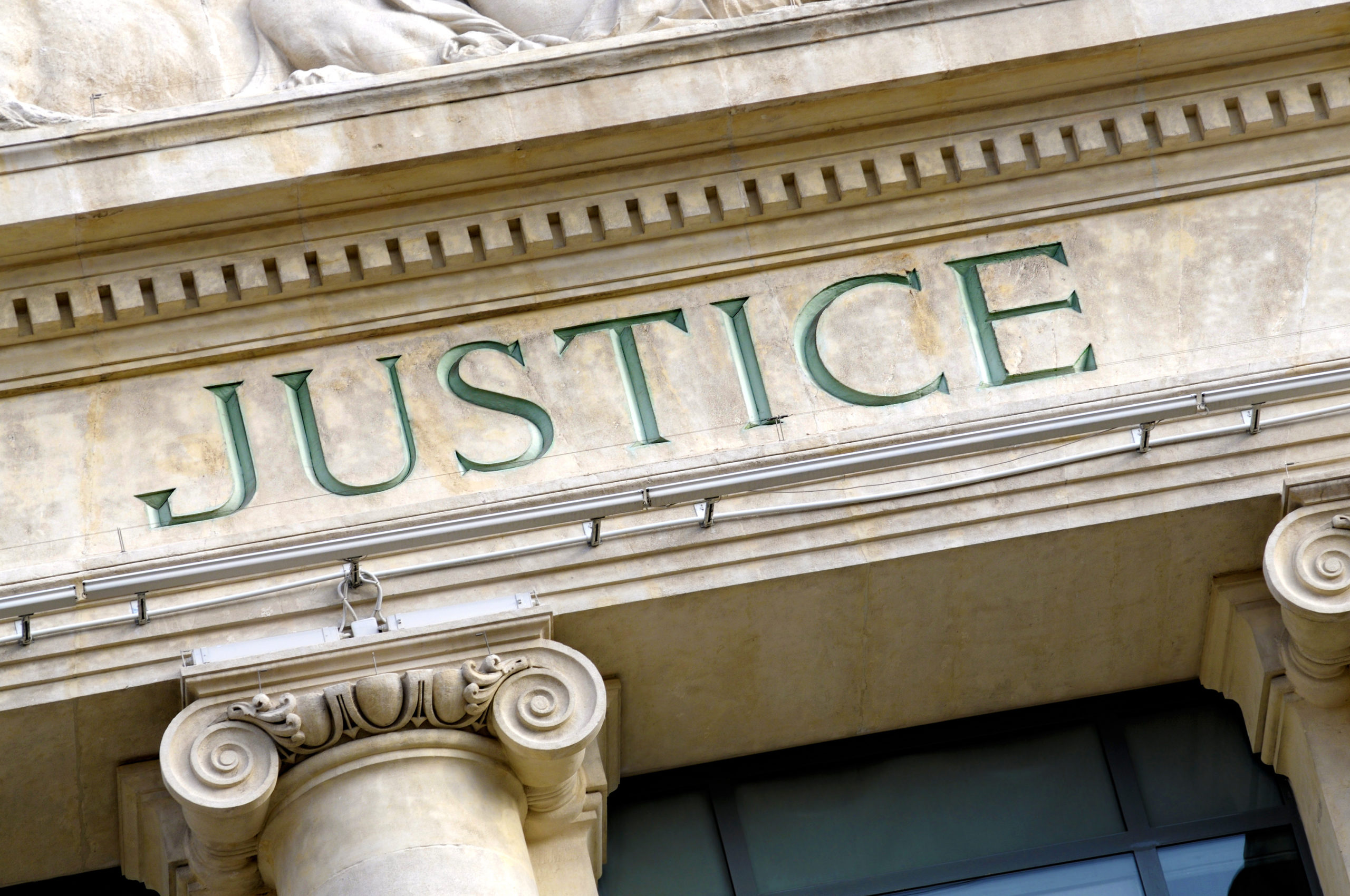 "the word ""justice"" engraved on the front of a court building"