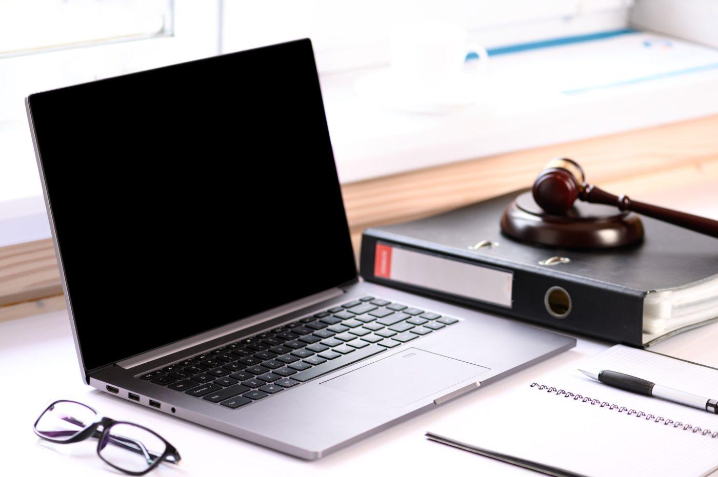 laptop with a pair glasses to the left, a binder with a gavel on top of it to the right, and a notebook in front of in front of it