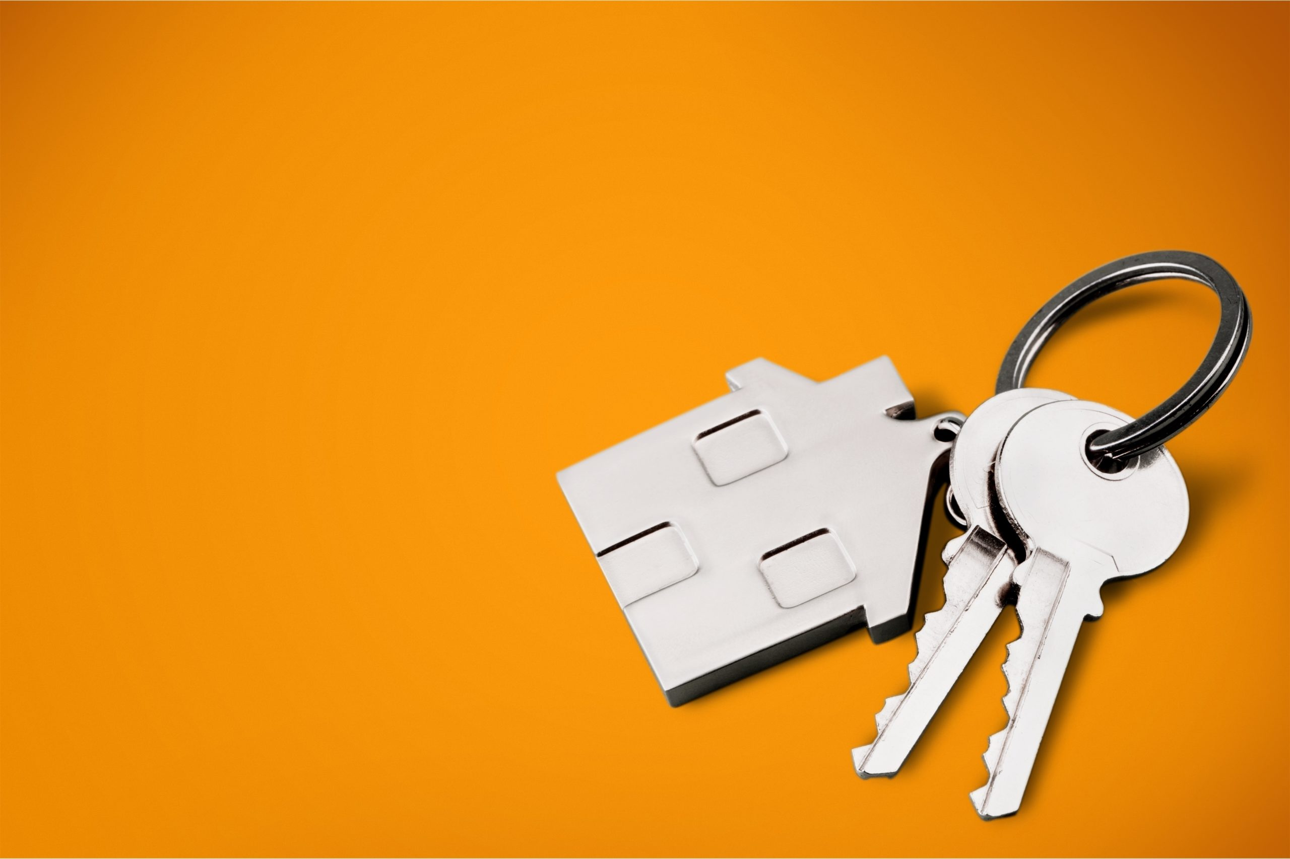 house shaped key chain and two keys on orange background