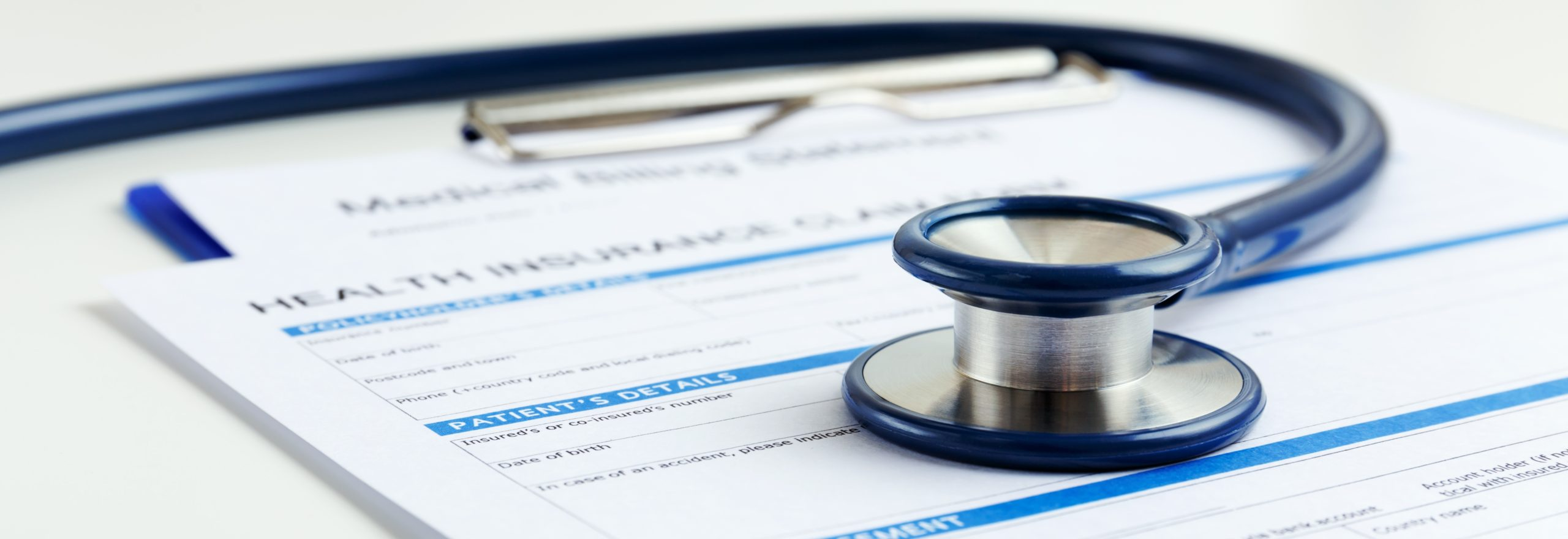 stethoscope on top of health insurance forms
